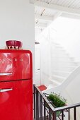 Red-painted, retro fridge and view into stairwell with white treads