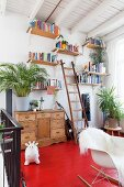 Red-painted wooden floor on gallery; wooden bookshelves on wall, classic rocking chair with white animal-skin rug