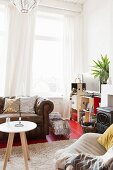 Side table on flokati rug in front of leather couch, airy curtains on windows in comfortable living room
