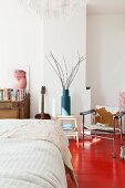 Bed with white bedspread and chair with animal skin cover on red-painted wooden floor