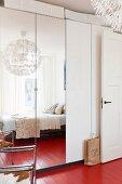 Wardrobe with mirrored doors in bedroom with red-painted wooden floor