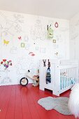 White cot on red-painted wooden floor and white wallpaper with line drawing motifs