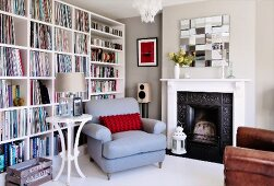 Pale blue armchair and round side table next to open fireplace and white bookcase against wall