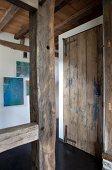 Doorway in timber structure and rustic wooden door in background