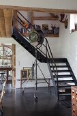 Vintage studio lamp on castors at foot of steel staircase in renovated half-timbered house belonging to artist