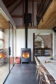 Rustic dining area below modern gallery in open-plan, renovated country house with fire in wood-burning stove