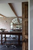 Vintage bar stools at wooden counter in front of arched mirror on brick wall