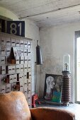 Vintage leather armchairs in front old apothecary cabinet in studio-style interior