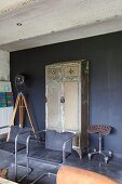 Retro cantilever chairs in front of vintage metal locker against wall painted dark grey
