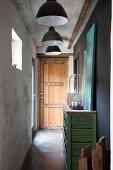 Narrow corridor with black pendant lamps in rustic, vintage interior