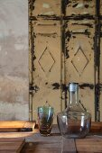 Glass carafe and stack of glasses on table in front of vintage metal locker