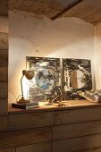 Artistic mirrors on sideboard lit by retro table lamp