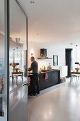 View through open door into kitchen with black base units, concrete floor and man stood at counter