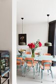 Flowers on dining table and wooden chairs with metal frames below two pendant lamps with metal lampshades
