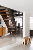 Wooden stool next to platform and metal staircase in contemporary interior