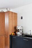 Espresso machine on black kitchen base unit next to wooden cupboard