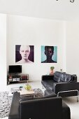 Black leather sofa and armchair around coffee table and large portraits on wall in minimalist interior