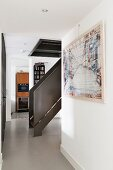 Staircase with solid, metal balustrade in narrow hallway