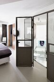 Glass and metal partition element: bed visible to one side
