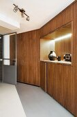 Long bank of fitted cupboards with backlit recess in minimalist interior