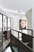 Landing with metal staircase balustrade and glass and metal partition with door