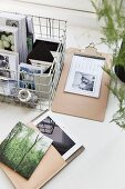 Postcards in wire basket next to blotter and tablet PC in case