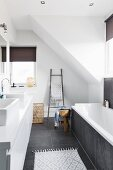 Designer, attic bathroom with large, grey floor tiles