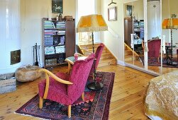 Fifties armchair, side table and standard lamp on rug in front of tiled stove