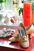 Gold shoes, red glass vase and glass container of semi-precious stones
