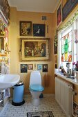 Yellow-painted bathroom with toilet, paintings with religious motifs on wall and ornaments on windowsill to one side