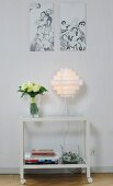 Pictures above lamp and vase of flowers on table on castors