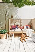 Dog sunbathing on rustic, sunny wooden deck in front of cosy couch with screened sides