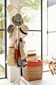 Collection of hats on tree-like coat stand, stacked baskets and open terrace door with view into garden