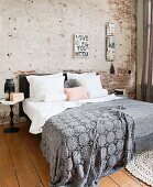 Grey crocheted bedspread on double bed against partially plastered brick wall in bedroom with wooden floor