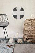Detail of black metal chair and basket on various grey rugs below stencilled motif on wall