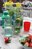 Glass and carafes with embossed pattern, candle lantern and bowl of strawberries on wooden table on roof terrace