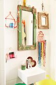 Jewellery hung from mirror frame with peeling paint and wire basket of bead necklaces and toiletries above small sink