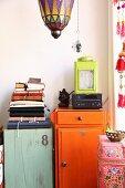 Oriental glass lantern above jumble of books on top of flea-market cabinets