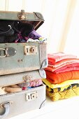Alternative clothes storage; stack of jumpers next to stuffed vintage suitcases