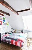 Bedroom with exposed ceiling beams, colourful children's drawings on wall and plain wooden floor