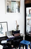 Storage boxes and drawing utensils on black, half-height shelves and blue, retro metal stool