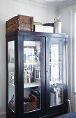 Books in glass-fronted cabinet with wooden crates and boxes on top on corner of room