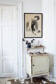 Small, vintage cabinet and wall bracket below framed drawing