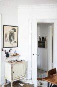 Small vintage cabinet, bracket shelf and framed drawing in corner behind open door