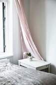 Shiny bedspread on bed, small table in corner and pink curtain
