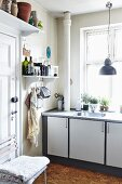 Detail of modern kitchen counter with sink below window and spices and utensils on wall-mounted shelf in vintage kitchen