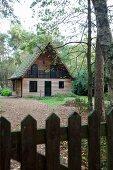 Blick über Gartenzaun auf Waldlichtung mit Zedernholz verkleidetes Holzhaus