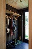 Blick durch Durchgang auf offene Garderobe in holzverkleidetem Hauseingang