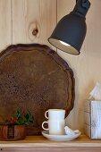 weiße Espressotassen und Vintage Tablett auf Ablage an Holzwand mit Wandleuchte