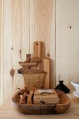 Massive Holzschale mit Küchenutensilien und Schneidebretter an Holzwand gelehnt